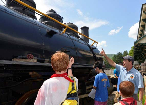 Bob Henderson points out the steam dome on the 1906 Baldwin locomotive to the Scouts BSAs